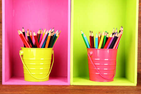 Colorful pencils in pails on shelves on wooden background Stock Photo - 18553851