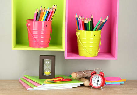 Colorful pencils in pails on shelves on beige background photo