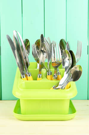 Knives, spoons, forks in plastic container for drying, on color wooden background Stock Photo - 18553818