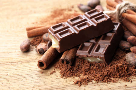 chocolate background: Composition of chocolate sweets, cocoa and  spices on wooden background
