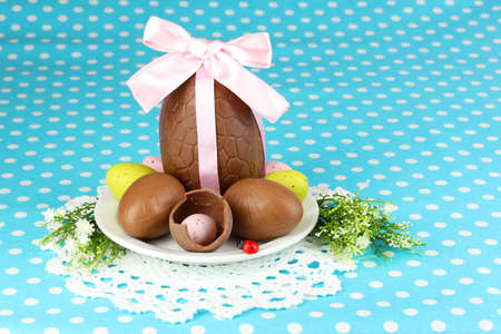 Composition of Easter and chocolate eggs on blue fabric background photo
