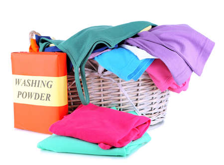 Clothes with washing powder in wooden basket isolated on white photo