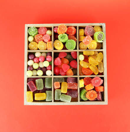 Multicolor candies in wooden box, on color background photo