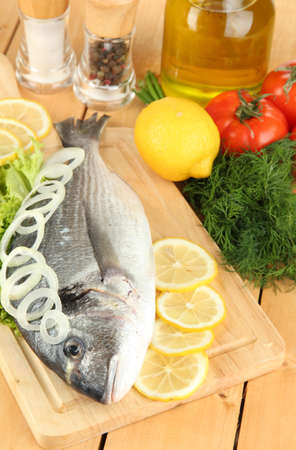 Fresh dorado on chopping board with lemon and vegetables on wooden table photo