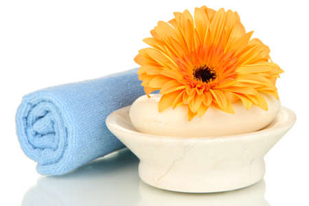 Rolled blue towel, soap bar and beautiful flower isolated on white