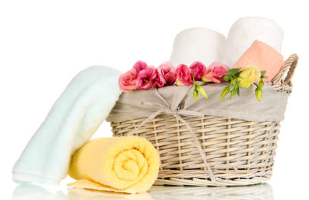 Bathroom towels folded in wicker basket isolated on white photo