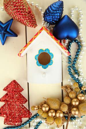 Nesting box and Christmas decorations on wooden background photo