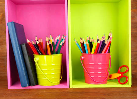 Colorful pencils in pails on shelves with writing-pad on wooden background photo