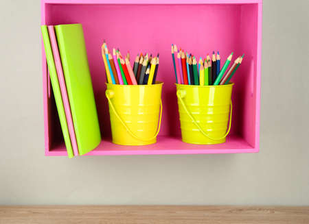 Colorful pencils in pails on shelf on beige background Stock Photo - 18579198