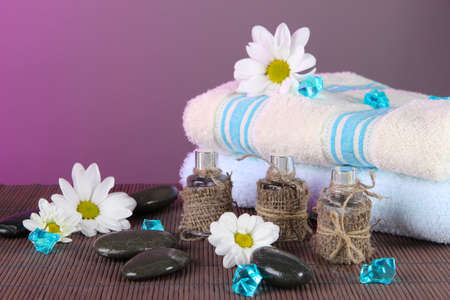 Oil spa towels on bamboo mat on pink background photo