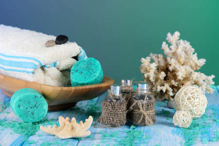 Oil spa, towels candles on wooden table on blue background photo