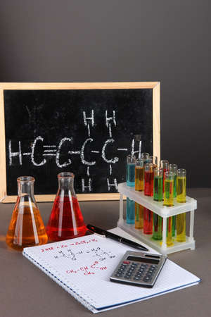 Test tubes with colorful liquids and formulas on grey background photo
