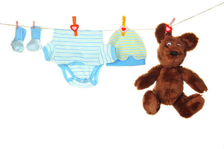 woman hanging toy: Baby clothes hanging on clothesline, isolated on white Stock Photo