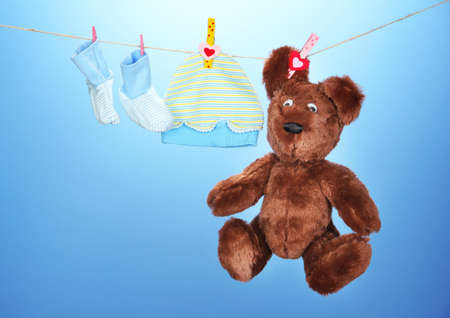 woman hanging toy: Baby clothes hanging on clothesline, on blue background