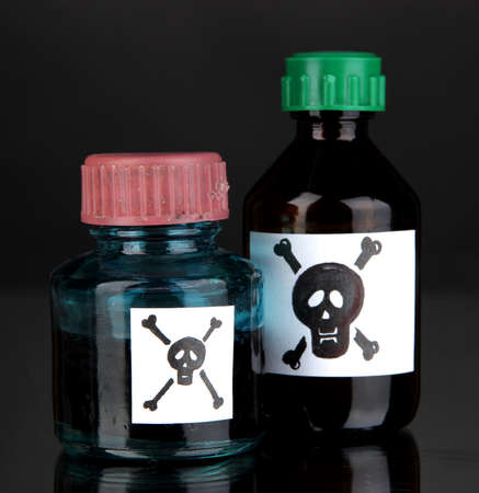 Deadly poison in bottles on black background photo