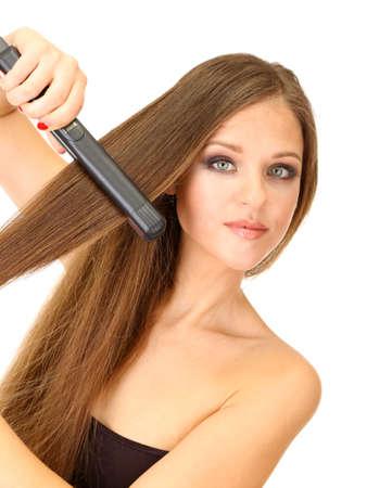 capelli lisci: Donna che fa acconciatura con il raddrizzatore dei capelli, isolato su bianco Archivio Fotografico