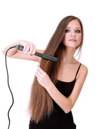 Woman doing hairstyle with hair straightener, isolated on white photo