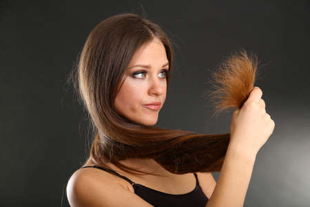 split: Beautiful woman holding split ends of her long hair,  on black background Stock Photo