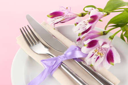 Festive dining table setting with flowers on pink background Stock Photo - 18579343