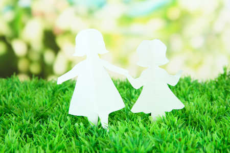 Paper people on green grass on bright background photo