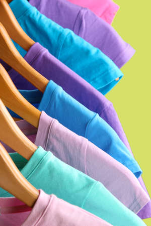 Lots of T-shirts on hangers on green background Stock Photo - 18579276