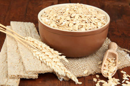 spikelets: Oat flakes in brown bowl on the table Stock Photo