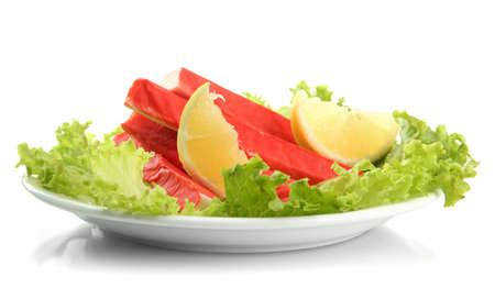 Crab sticks with lettuce leaves and lemon on plate isolated on white Stock Photo - 18605194
