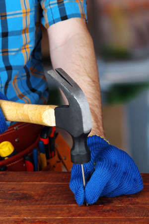 Builders hands hammering nail into wood
