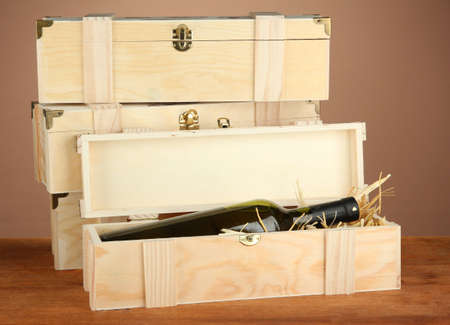 Wine bottle in wooden box on wooden table on brown background Stock Photo - 18605613