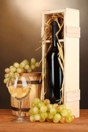 Wooden case with wine bottle, barrel, wineglass and grape on wooden table on brown background photo
