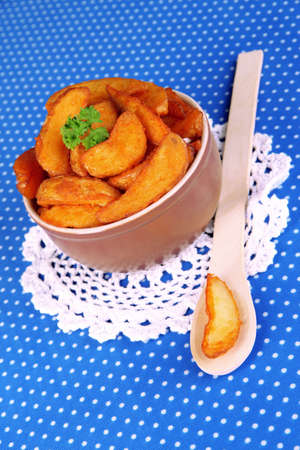 nutritiously: Appetizing village potatoes in bowl on blue fabric close-up