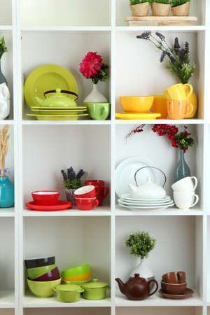 Beautiful white shelves with tableware and decor  Stock Photo - 18605555