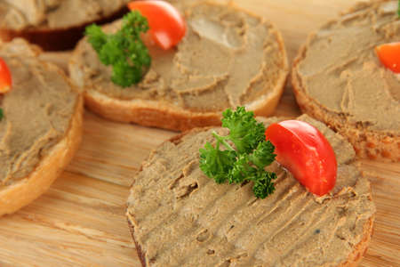 Fresh pate on bread on wooden board, close up photo