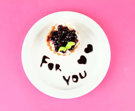 Sweet cake with blackberry and chocolate sauce on plate, on color background photo
