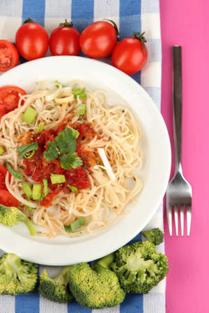 Tasty spaghetti with sauce and vegetables on plate on wooden table close-up photo