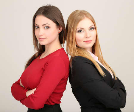 Two business women on grey background Stock Photo