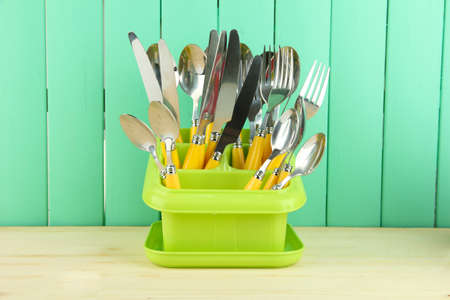 Knives, spoons, forks in plastic container for drying, on color wooden background Stock Photo - 18605620