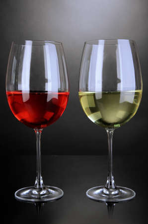 stemware: Red and white wine in glasses on grey background