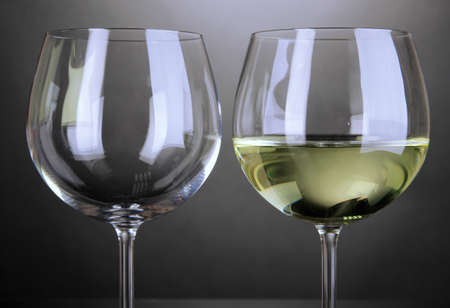 stemware: Empty and full wine glass on grey background