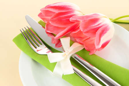 Festive dining table setting with tulips on beige background photo