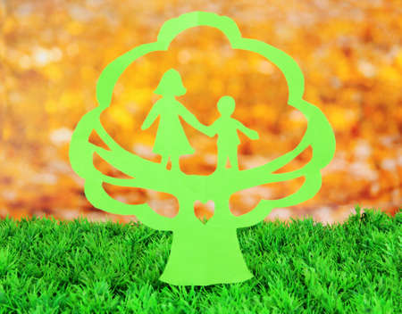 Green cut out paper tree with people inside, on green grass on bright background photo
