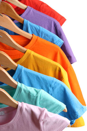 Lots of T-shirts on hangers isolated on white photo