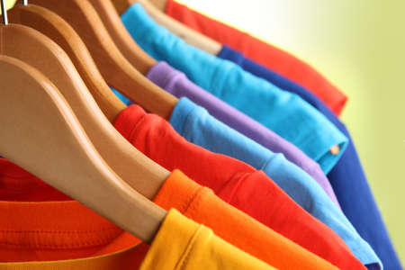 Lots of T-shirts on hangers on green background Stock Photo - 18610335
