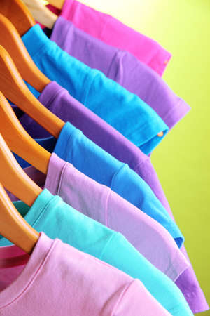 Lots of T-shirts on hangers on green background Stock Photo - 18610375