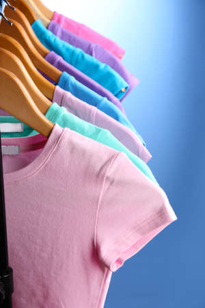 Lots of T-shirts on hangers on blue background Stock Photo - 18610376