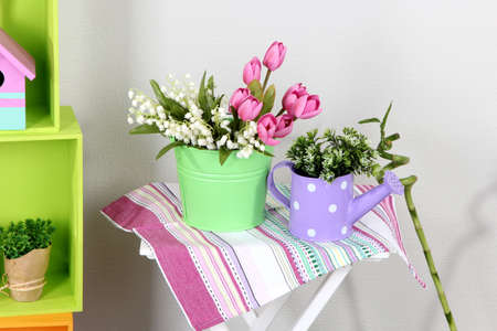 Colorful shelves and table with decorative elements and flowers photo