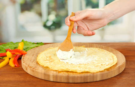 smears: Process of preparing egg rolls, on bright background: female hand smears cheese cream on omelet