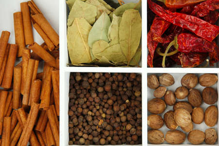 Assortment of aroma spices in white wooden box close up photo