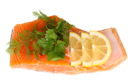 Fresh salmon fillet with herbals and lemon slices, isolated on white photo