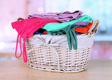 Clothes in wooden basket on table in room Stock Photo - 18606259